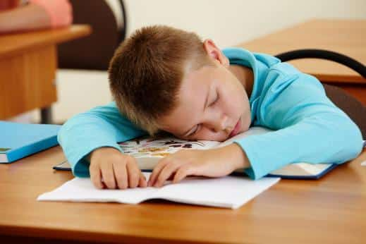 a baby boy sleeping on his desk in school